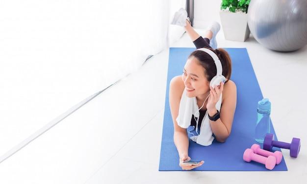 Donna asiatica che ascolta la musica con la cuffia e lo smartphone dopo yoga ed esercizio del gioco a casa. Foto Premium