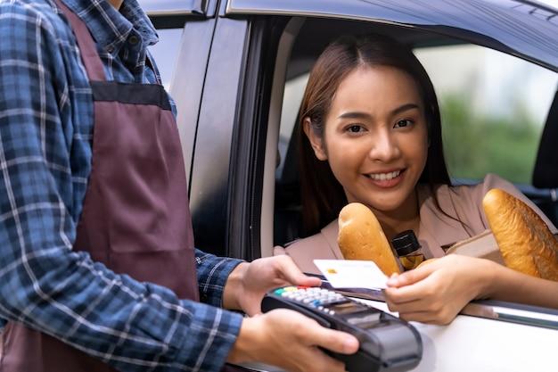 Donna asiatica che effettua pagamento senza contatto per la drogheria Foto Premium
