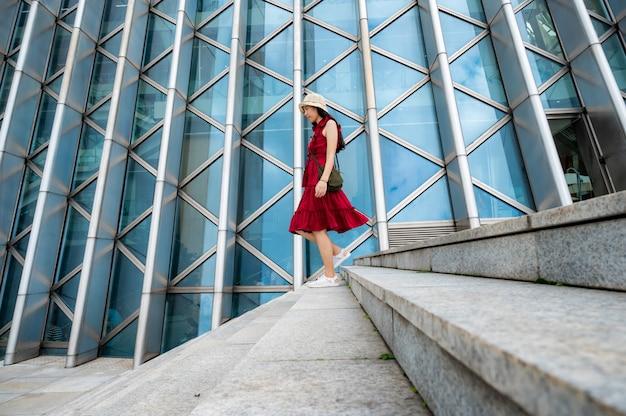 Donna asiatica in abito rosso in edificio moderno, ragazza femminile con lo stile di vita urbano della città Foto Premium