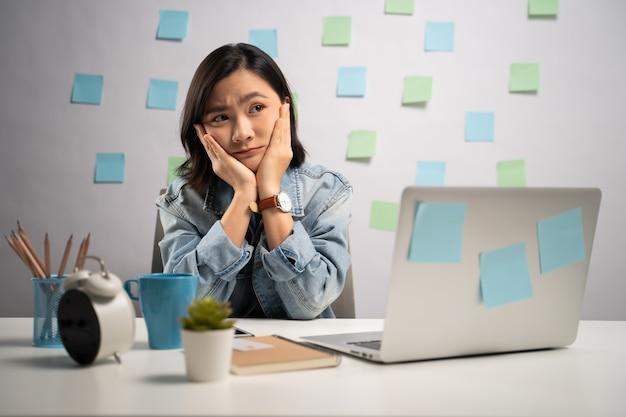 Donna asiatica che lavora seriamente su un computer portatile in ufficio a casa. . lavoro da casa. concetto di prevenzione coronavirus covid-19. Foto Premium