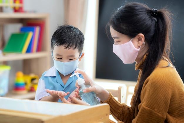 Insegnante di donna asiatica usa gel alcolico a disposizione del suo studente per prevenire il virus da covid19 in classe in età prescolare. Foto Premium