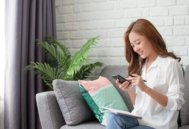 Donna asiatica che utilizza il telefono per contattare le persone. Foto Premium