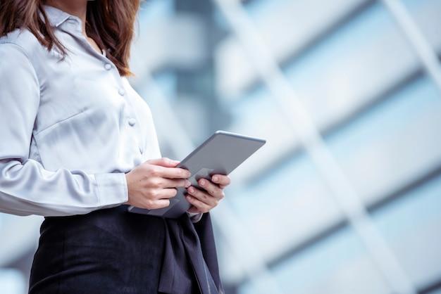 Donna asiatica utilizzando tablet shopping sito web online su smartphone con volto sorridente. Foto Premium