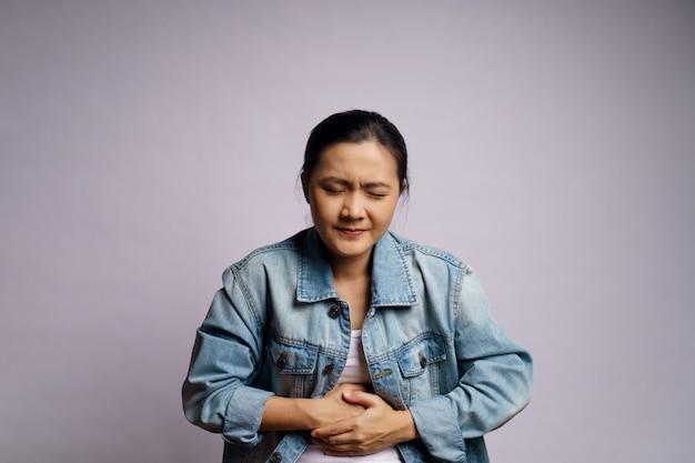 La donna asiatica era malata di mal di stomaco in piedi isolata. Foto Premium