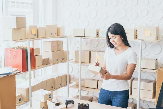 Donna asiatica che lavora a casa con i contenitori di imballaggio Foto Premium