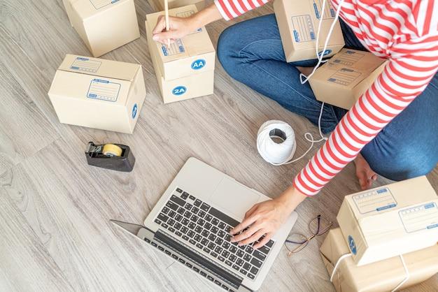 Imprenditore di donne asiatiche che lavora a casa con scatola di imballaggio sul posto di lavoro, imprenditore di pmi dello shopping online o concetto di vendita online Foto Premium