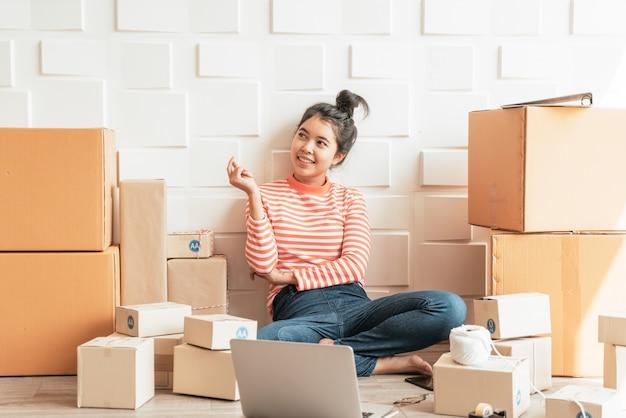 Imprenditore asiatico delle donne che lavora a casa con il contenitore di imballaggio sul posto di lavoro Foto Premium