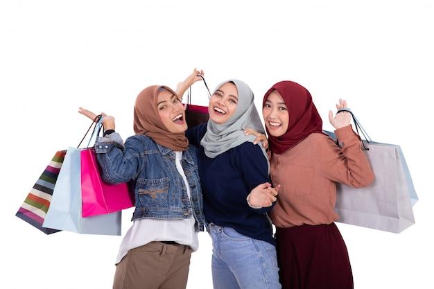 Giovani donne velate asiatiche che trasportano un certo sacco di carta dopo la compera Foto Premium