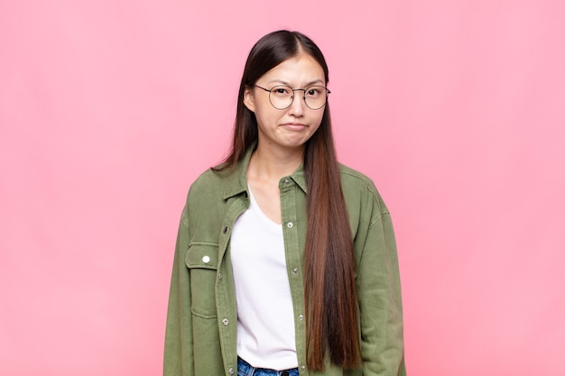 Giovane donna asiatica che si sente confusa e dubbiosa, chiedendosi o cercando di scegliere o prendere una decisione Foto Premium