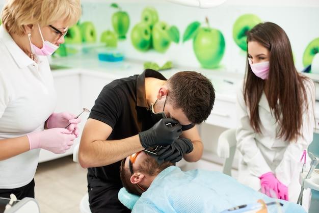 L'assistente dentista in presenza di un medico prepara il paziente a rimuovere il dente Foto Premium