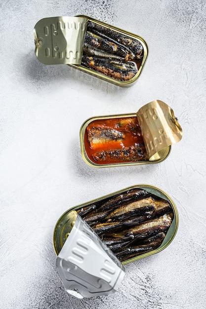 Conserve di pesce in scatola di latta sardine, sardine affumicate, sgombri. fondo di legno grigio. vista dall'alto. Foto Premium