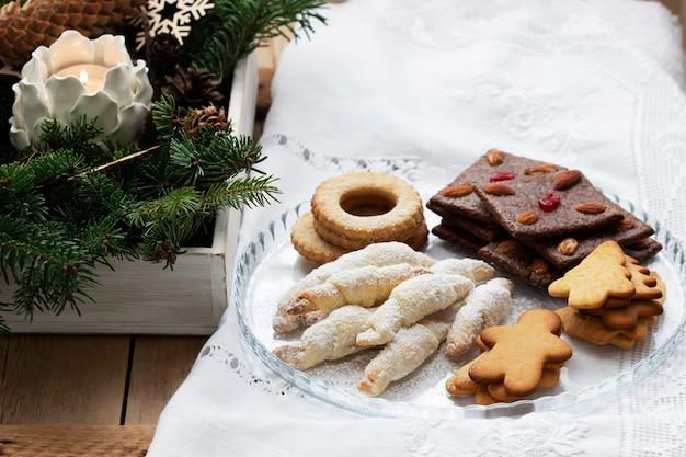 Biscotti assortiti, rami di abete e una ghirlanda su sfondo chiaro. stile rustico, messa a fuoco selettiva. Foto Premium