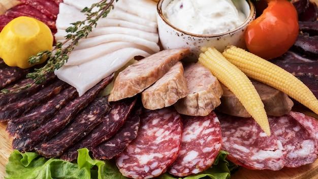 Assortimento di salsicce con verdure sottaceto su tavola di legno. avvicinamento Foto Premium