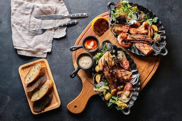 Frutti di mare assortiti sui piatti. bella composizione su un tavolo servito di pesce, calamari, gamberi, bistecca di salmone e polpo. foto di cibo, bassa chiave, cucina tradizionale italiana. vista dall'alto, risparmia spazio. Foto Premium