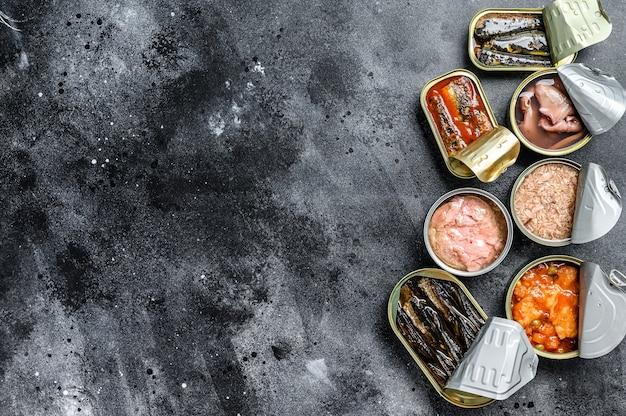 Assortimento di lattine, in scatola con diversi tipi di pesce e frutti di mare. sfondo nero. Foto Premium