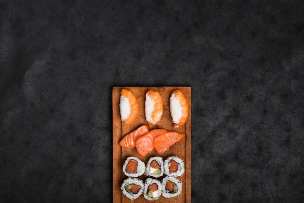 Assortimento di sushi sul vassoio in legno contro il contesto di texture nero Foto Premium