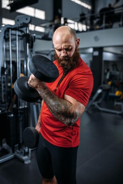 Atleta che fa esercizio con manubri in palestra Foto Premium