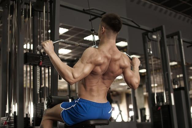 Atleta bodybuilder muscolare allenamento torna sul simulatore in palestra Foto Premium