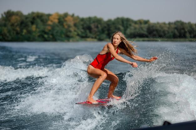 Donna bionda atletica che pratica il surfing a bordo giù l'acqua blu Foto Premium