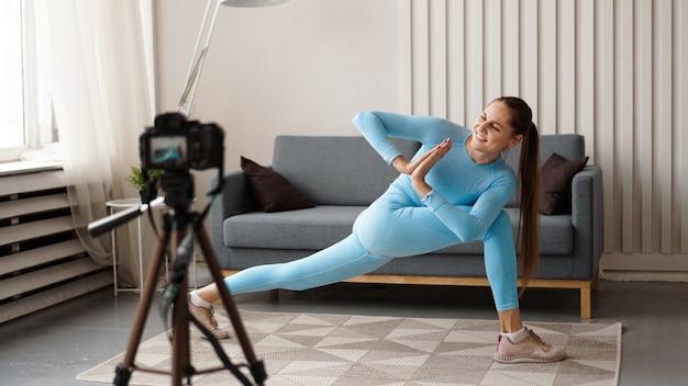 Blogger donna atletica in abbigliamento sportivo gira video sulla fotocamera a casa in salotto. concetto di sport e ricreazione. uno stile di vita sano. Foto Premium