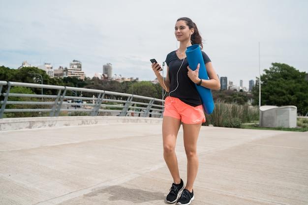 Donna atletica che tiene una stuoia di addestramento Foto Premium
