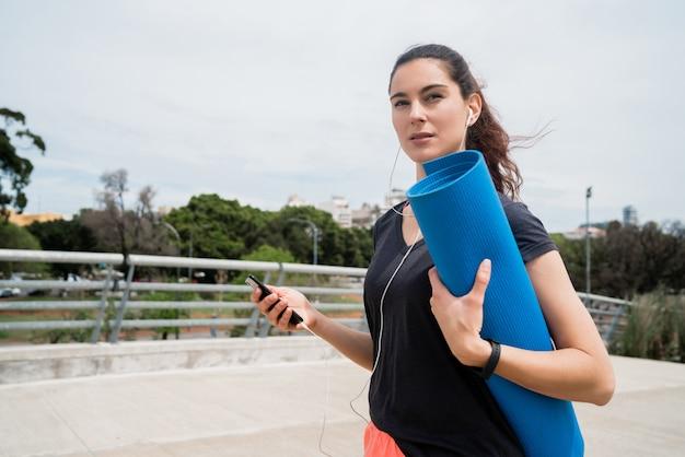 Donna atletica che tiene una stuoia di addestramento. Foto Premium