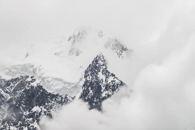Atmosferico paesaggio alpino minimalista con massiccio ghiacciaio sospeso sulla cima della montagna innevata Foto Premium