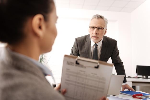Uomo attento che indossa un costume intelligente e occhiali premendo le labbra mentre guarda la sua segretaria Foto Premium