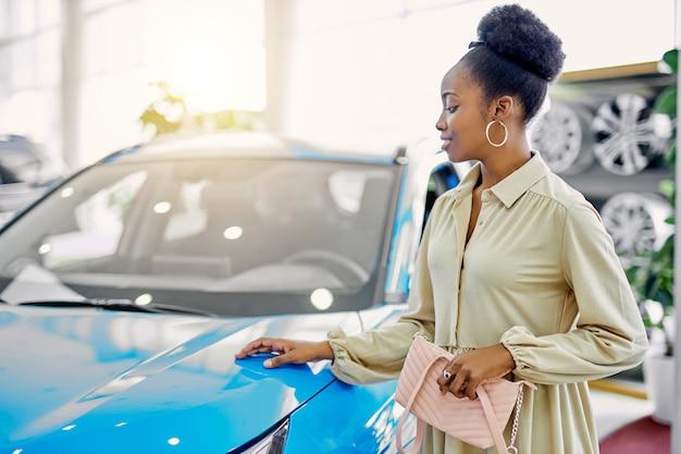 Attraente donna afro sogna una nuova auto Foto Premium