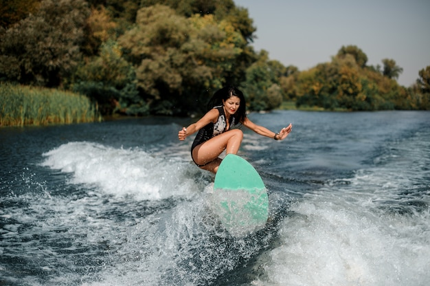Donna attraente del brunette che pratica il surfing a bordo giù l'acqua blu Foto Premium