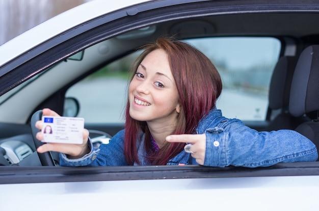 Attraente ragazza caucasica seduto in macchina tenendo la patente di guida Foto Premium