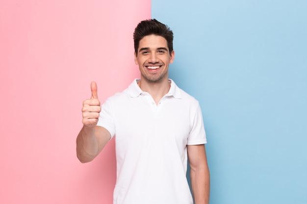 Uomo attraente con stoppie che mostra il pollice in alto con un sorriso felice, isolato su un muro colorato Foto Premium