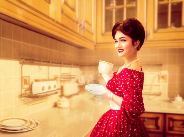 Attraente ragazza pinup con trucco beve il caffè sulla caffetteria della cucina, 50 moda americana. abito rosso con pois, stile vintage Foto Premium
