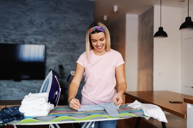 Casalinga bionda sorridente attraente in piedi in soggiorno e stirare i vestiti. Foto Premium