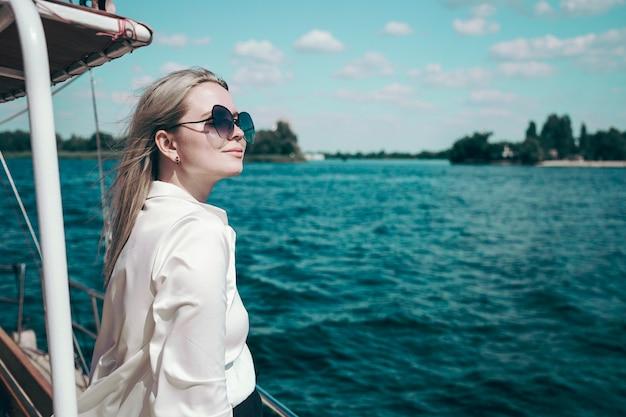 Attraente ragazza sorridente in una camicia bianca e occhiali da sole su uno yacht Foto Premium