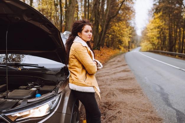 Bruna dai capelli afro sconvolto attraente accanto alla sua macchina rotta nella foresta sulla strada vuota Foto Premium