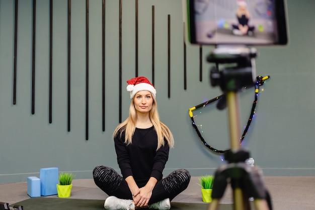 Attraente blogger donna al cappello di babbo natale in abbigliamento sportivo registra esercizi per l'allenamento per il suo vlog. Foto Premium
