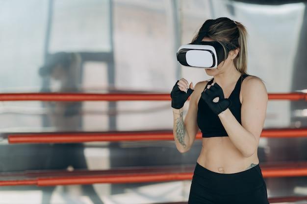 Pugilato attraente della donna nell'addestramento della cuffia avricolare di vr 360 per dare dei calci alla realtà virtuale Foto Premium