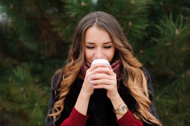 La donna attraente ha una pausa caffè sulla strada nel giorno di autunno. Foto Premium