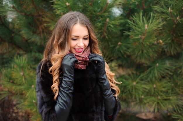 Donna attraente che cammina nel parco nel giorno di autunno Foto Premium