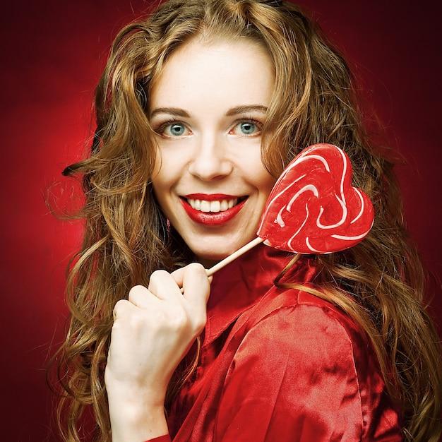 Donna attraente con caramello cuore su rosso Foto Premium