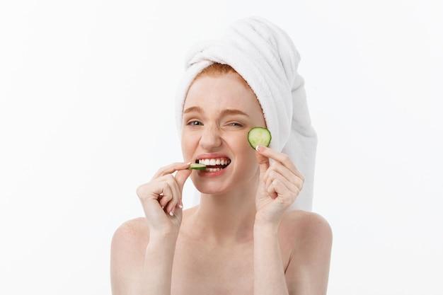 Attraente giovane donna con una bella pelle pulita. maschera bianca e cetrioli Foto Premium
