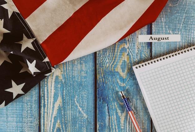 Mese di agosto dell'anno civile bandiera degli stati uniti d'america del simbolo di libertà e democrazia con il blocco note e la penna in bianco sulla tavola di legno dell'ufficio Foto Premium