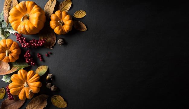 Decorazione di sfondo autunnale da foglie secche e zucca Foto Premium