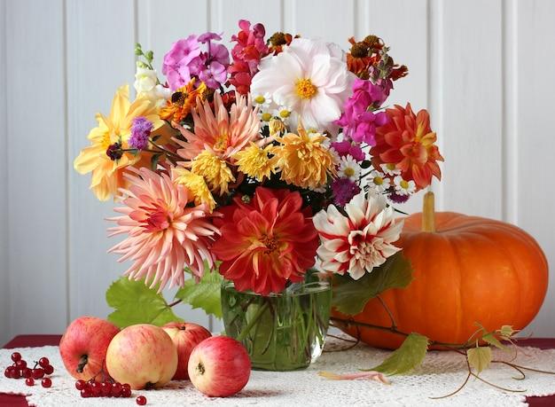 Luce autunnale ancora in vita con un bouquet di fiori, mele e zucca sul tavolo. raccolto, abbondanza. Foto Premium