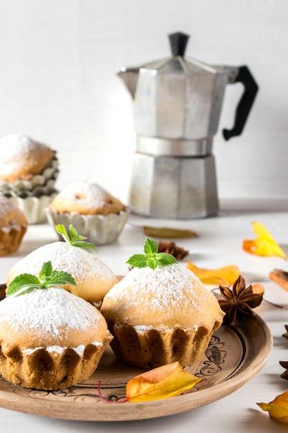 Pasticcini autunnali. cupcakes fatti in casa con zucchero a velo con bastoncini di cannella, anice stellato e foglie di autunno Foto Premium