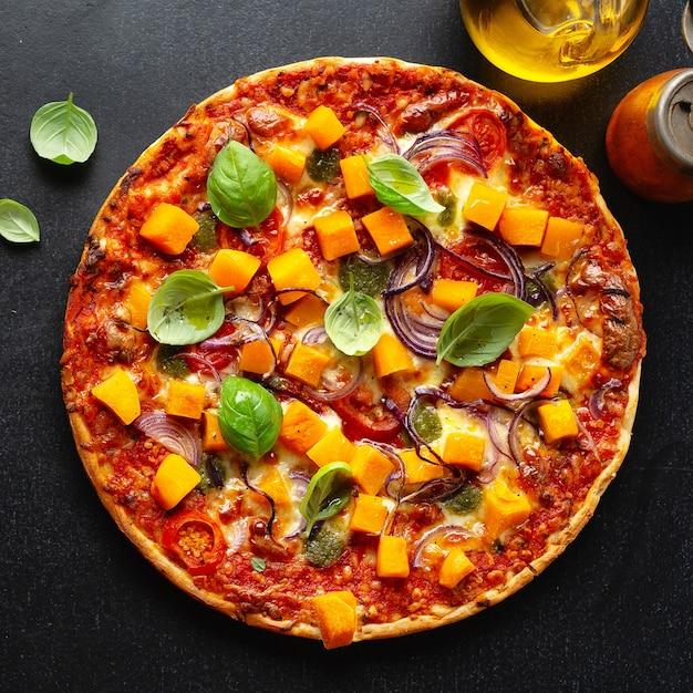Pizza vegetariana autunnale con zucca e verdure su sfondo scuro. piazza. Foto Premium