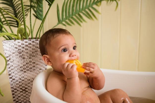Il bambino fa il bagno in una vasca da bagno e mangia un'arancia su una parete di legno Foto Premium