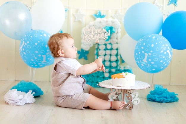Bambino 1 anno in uno studio fotografico con una torta e palloncini, compleanno di un bambino 1 anno, il bambino mangia la torta Foto Premium