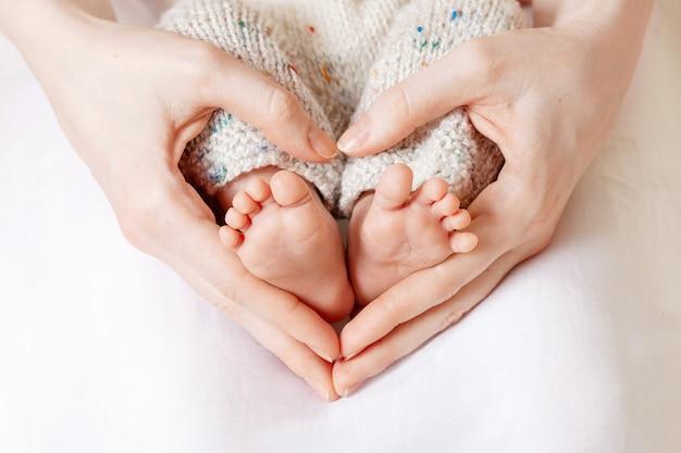 Piedi del bambino nelle mani della madre. i piedi del neonato piccolo sul primo piano delle mani a forma di cuore femminile Foto Premium